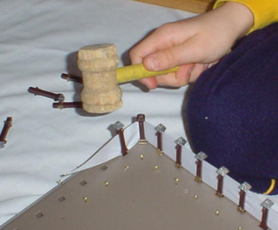 Photo demonstrating tapping in the post in the tabernacle kit fence
