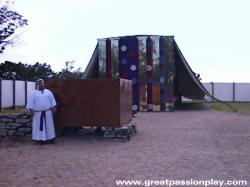 Great passion Play image of priest standing by the altar in front of the Tabernacle model